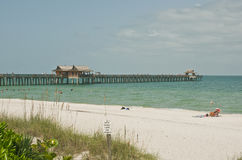 Beach and fishing pier on a tropical day in the Gulf of Mexico. Beach and fishing pier on a tropical day with sunbathers and swimmers in the Gulf of Mexico Stock Photos