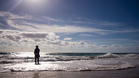 Beach Fishing. Silhouette of an unidentified man fishing on a beach on a late morning. Photo taken on December 22nd, 2014 royalty free stock image