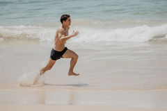 Beach fitness man runner running training cardio. Healthy lifestyle male athlete doing exercise living an active life working out Royalty Free Stock Photography