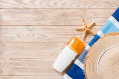 Beach flat lay accessories with copy space. Striped blue and white towel, seashells, staw sunhat and a bottle of sunblock on. Wooden background. Summer holiday stock photos