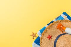 Beach flat lay accessories with copy space. Striped blue and white towel, seashells, staw sunhat and a bottle of sunblock on. Yellow background. Summer holiday royalty free stock image