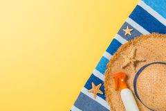 Beach flat lay accessories with copy space. Striped blue and white towel, seashells, staw sunhat and a bottle of sunblock on. Yellow background. Summer holiday royalty free stock images