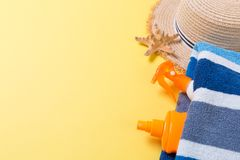 Beach flat lay accessories with copy space. Striped blue and white towel, seashells, staw sunhat and a bottle of sunblock on. Yellow background. Summer holiday stock photography