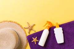 Beach flat lay accessories with copy space. Violet blue and white towel, seashells, staw sunhat and a bottle of sunblock on yellow. Beach flat lay accessories royalty free stock photography