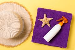Beach flat lay accessories with copy space. Violet blue and white towel, seashells, staw sunhat and a bottle of sunblock on yellow. Beach flat lay accessories stock photography