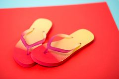 Beach flip flop on red background. Pair of colorful flip flops on coral background. Summer, vacation, beach, shoes, shop concept. Studio shot of pink yellow royalty free stock photos