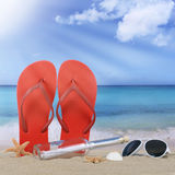 Beach with flip flops sandals and bottle post in summer vacation Royalty Free Stock Image