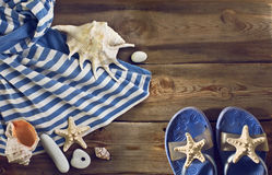 Beach flip flops, striped dress, seashells on a wooden floor. Royalty Free Stock Images