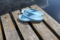 Beach flip flops on a wooden lake bridge Royalty Free Stock Image
