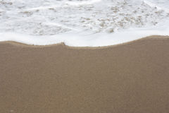 Beach with foam Royalty Free Stock Image
