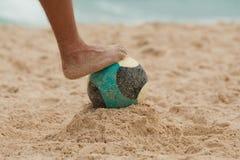 Beach football. Leg on football on a beach Stock Photo