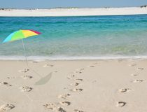 Beach Footprints and Umbrella. Colorful beach umbrella next to three sets of footptrints leading to pretty ocean water Royalty Free Stock Photos