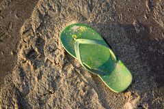 Beach Footwear. A green flipflop lying in the beach sands Stock Photography