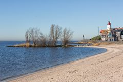 Beach of former island Urk with view at historic Lighthouse stock image