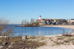 Beach of former island Urk with view at historic Lighthouse royalty free stock photo