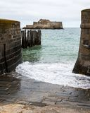 The beach and Fort National during high tide in Saint Malo. Bretagne, France on a stormy, cloudy day in summer stock images