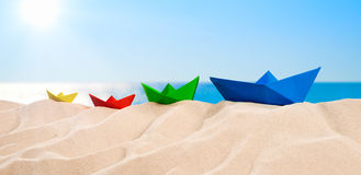 On the Beach - Four colorful paper boats on a sand dune Royalty Free Stock Photo