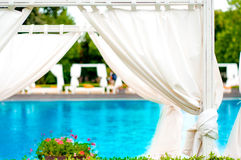 Beach front relaxing sunbeds inside tent at fancy pool Stock Photo