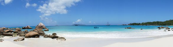 Beach in front of the Seychelles white sail boat sails on the blue sea Stock Images