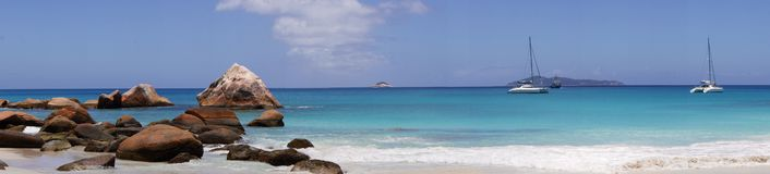 Beach in front of the Seychelles white sail boat sails on the blue sea Royalty Free Stock Photography