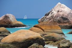 Beach in front of the Seychelles white sail boat sails off the coast on the blue sea Stock Images