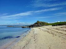 Beach in front of a small rocky hill. Sandy beach on Motuihe Island near Auckland with a small rocky hill in the background Stock Images