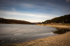 Beach by the frozen lake. Beautiful sunny winter day. royalty free stock image