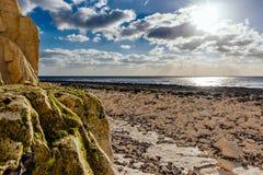Calm beach full of rocks stock images