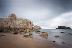 Beach full of rocks with cloudy sky, Spain Stock Image