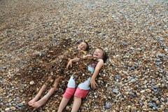 Beach fun. Kids having fun with pebbles Stock Photo