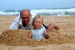 Beach fun. An elderly Caucasian man and a little blond blue eyed girl with cute and happy expression in the face playing together in the sand of the beach during Stock Photo