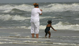 Beach Fun. Woman and child enjoying the rough surf at the beach Stock Photo