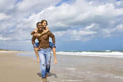 Beach fun. Man carrying woman on his back on a beach Stock Photos