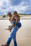 Beach fun. Man carrying woman on his back on a beach Stock Image