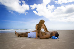 Beach fun. Man laying on a beach, woman sitting next to him Royalty Free Stock Photos
