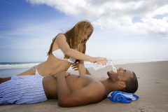 Beach fun. Man laying on a beach, woman sitting next to him Stock Image