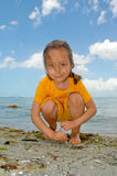 Beach fun. Girl drawing on the sand with a Sunshine Skyway bridge over Tampa Bay, Florida in background Stock Images
