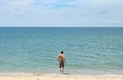Beach Fun. A man running into the blue water on a beach Stock Photos