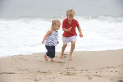 Beach Fun. Two blond kids running at the beach Royalty Free Stock Photos