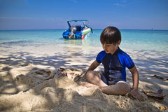 Asian boy on the beach sitting and playing with sand Royalty Free Stock Photo