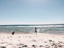 Beach fun. Brother playing at the ocean Stock Photos