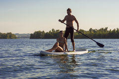 Beach fun couple on stand up paddle board SUP07. Sports men and women on vacation sport on stand up paddle board SUP newlyweds Stock Image