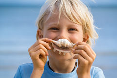 Beach fun, cute child holding shell over his mouth stock images