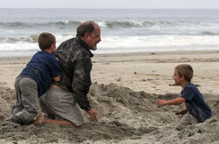 Beach Fun - Grand Father and Grand Sons. A grand father wrestles with his grandsons in the sand on the beach at Imperial Beach near the pier with the surf stock photography