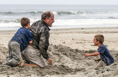 Beach Fun - Grand Father and Grand Sons. A grand father wrestles with his grandsons in the sand on the beach at Imperial Beach near the pier with the surf royalty free stock photo