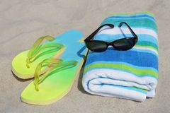 Beach gear. Flip-flops, sunglasses and a towel on a sandy beach Royalty Free Stock Photos