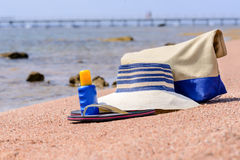 Beach gear on the sand overlooking the sea. With a sunhat, sunscreen, slip slops and beach bag conceptual of a summer vacation in the tropics Royalty Free Stock Photo