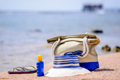 Beach gear on the sand overlooking the sea. With a sunhat, sunscreen, slip slops and beach bag conceptual of a summer vacation in the tropics Royalty Free Stock Image