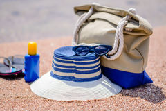 Beach gear on the sand overlooking the sea. With a sunhat, sunscreen, slip slops and beach bag conceptual of a summer vacation in the tropics Royalty Free Stock Images