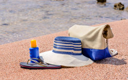 Beach gear on the sand overlooking the sea. With a sunhat, sunscreen, slip slops and beach bag conceptual of a summer vacation in the tropics Stock Photo